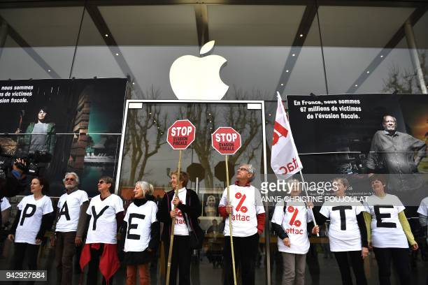 Activists of the Association for the Taxation of financial Transactions and Citizen's Action stand in front of the Apple store during a protest...