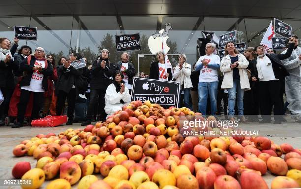 TOPSHOT Activists of the Association for the Taxation of financial Transactions and Citizen's Action stand next to apples and signs reading 'pay your...
