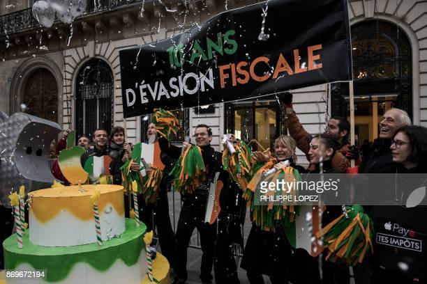 Activists of the 'Attac' network hold a sign reading '10 years of tax evasion' during a protest outside an Apple shop on the release day of the new...