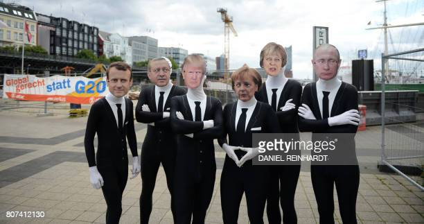 Activists of the 'Attac' network wear masks of French President Emmanuel Macron Turkish President Recep Tayyip Erdogan US President Donald Trump...