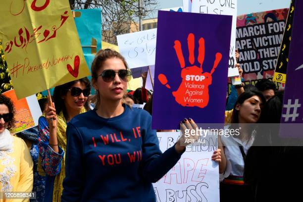 Activists of the Aurat March hold placards as they march during a rally to mark International Women's Day in Lahore on March 8, 202 - Demonstrators...