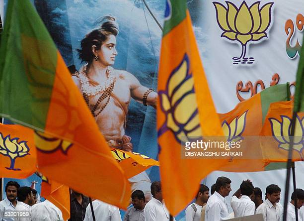 Activists of the Bhartiya Janta Party wave party flags in front of a billboard depicting the Hindu God Ram during a protest rally organised by the...