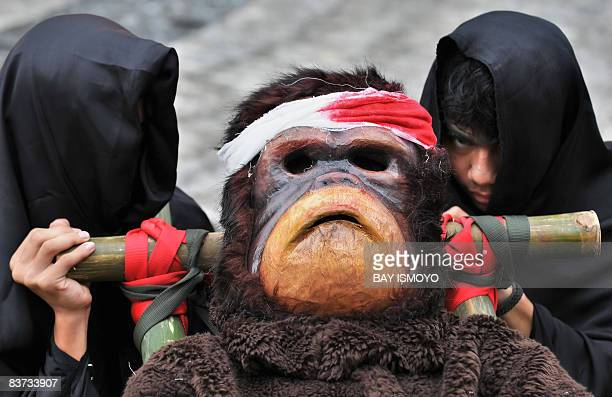 Activists of the Centre for Orangutan Protection dressed as injured orangutans take part in a demonstration against the Roundtable on Sustainable...