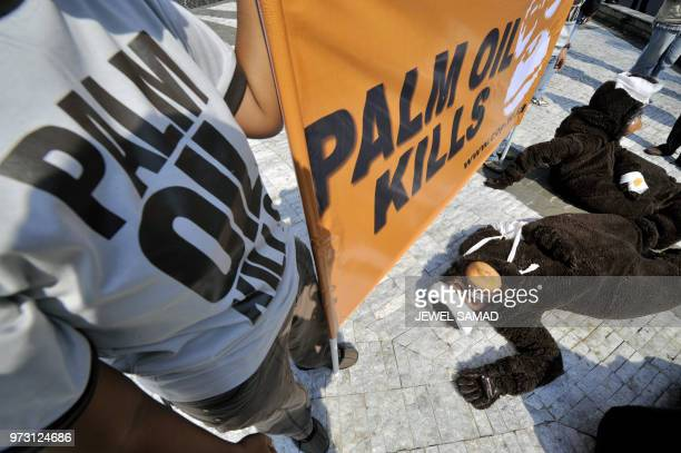 Activists of the Centre for Orangutan Protection dressed as injured orangutans lay on the ground as other display a banner during a demonstration in...