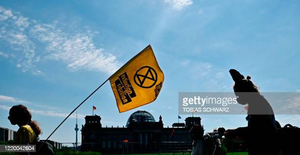 Activists of the Extinction Rebellion movement demonstrate in front of the Reichstag building housing the Bundestag to protest against the German...