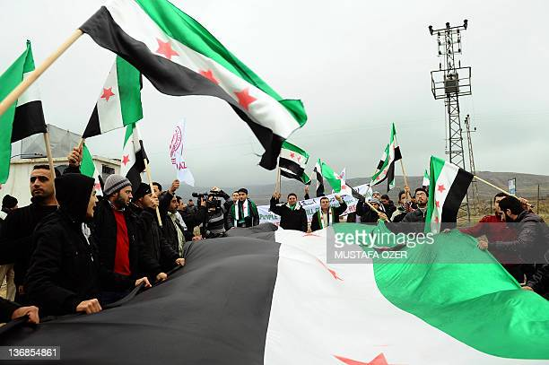 Activists of the Freedom Convoy wave independence flags and chant slogans against during a gathering near the TurkishSyrian border city of Kilis on...
