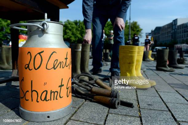 Activists of the German Dairy Farmers Association set up rubber boots and a milk can with the inscription '20 cent you should be ashamed' in front of...