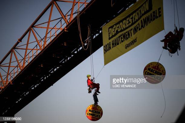 """Activists of the Greenpeace ecologist organisation deploy a banner reading """"Deforestation, highly flammable soybeans"""" as they block the entrance..."""