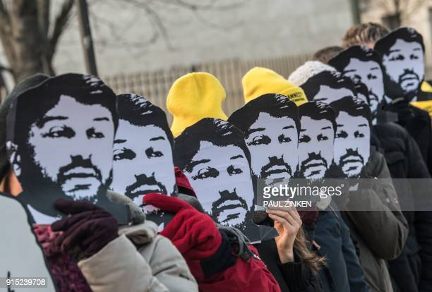 TOPSHOT Activists of the human rights organisation Amnesty International hold masks of Turkish civil rights activist Taner Kilic in front of their...