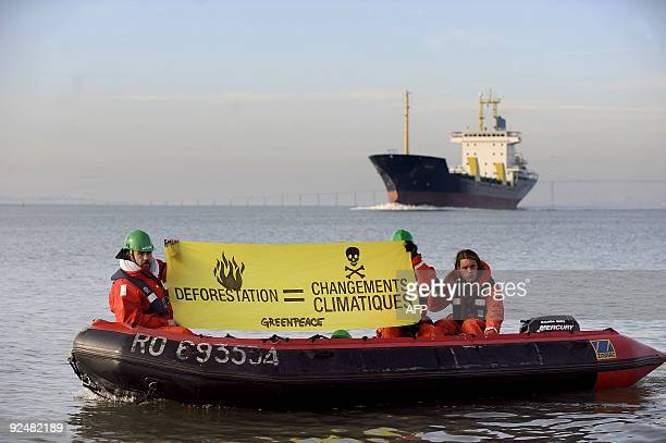 Activists of the international ecological Greenpeace organisation hold a banner aboard a Zodiac in the Saint-Nazaire harbor, western France, on...