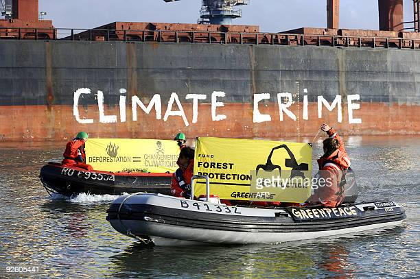 Activists of the international ecological Greenpeace organisation hold banners aboard Zodiacs in the Saint-Nazaire harbor, western France, on October...