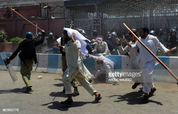 TOPSHOT Activists of the Jamiat UlemaeIslamFazl party run from policemen during a protest against the amendment bill on semiautonomous Federally...