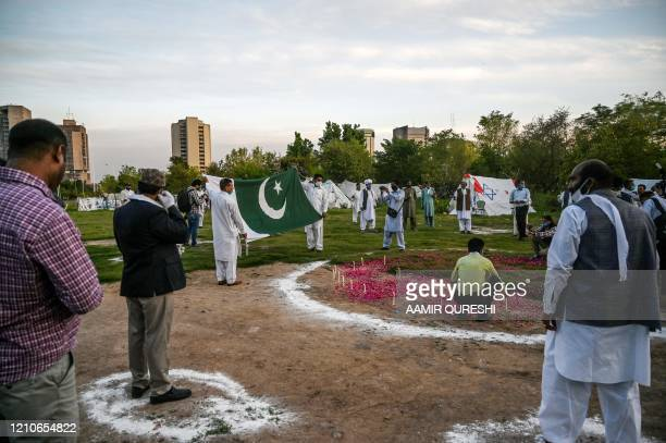 Activists of the minority wing of the Pakistan Tehreek-e-Insaf political party stand in circle as they pray asking for the end of the coronavirus...