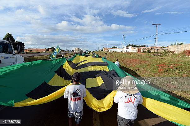 Activists of the Movimento Brasil Livre carry a huge banner along the BR-020 highway during the March for Freedom that demands the impeachment of...