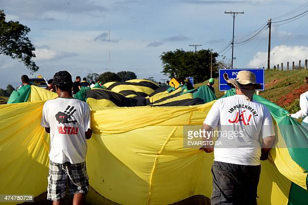 Activists of the Movimento Brasil Livre march deploying a huge banner along the BR-020 highway during the March for Freedom that demands the...