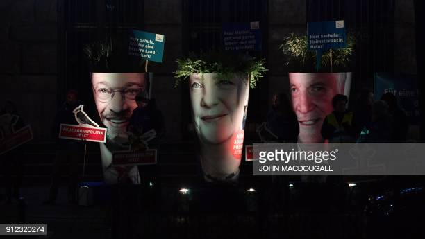 TOPSHOT Activists of the Naturbundschutz protest with giant portraits of leader of the Social Democratic Party Martin Schulz German Chancellor and...