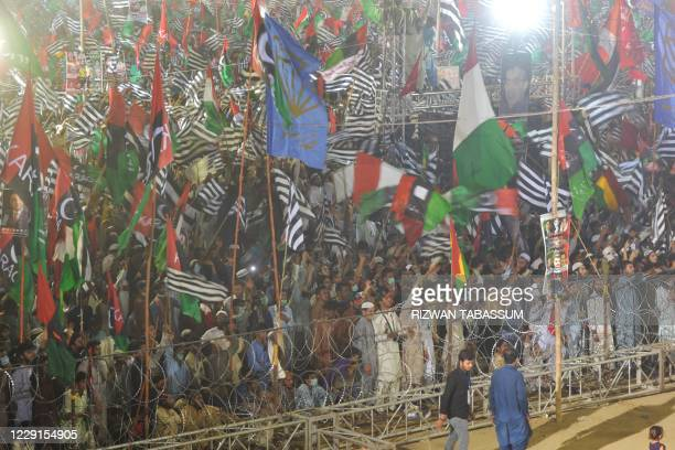 Activists of the newly-formed Pakistan Democratic Movement , an opposition alliance of 11 parties, wave parties flags during the public rally in...