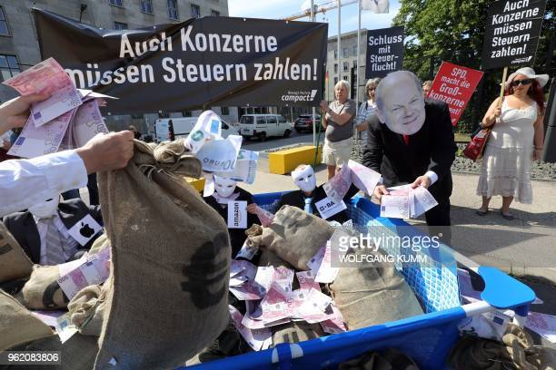 Activists of the nongovernmental organization Campact take part in a protest against the failure in the fight against tax evasion in front of the...
