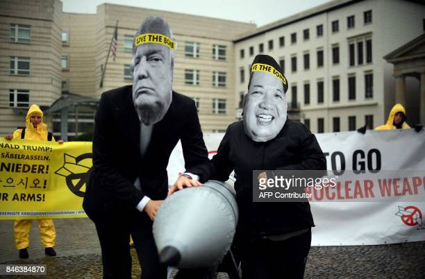 Activists of the nongovernmental organization 'International Campaign to Abolish Nuclear Weapons ' wear masks of US President Donal Trump and leader...