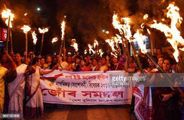 Activists of the North East Women Front take part in a torch light procession in protest against the Citizenship Bill 2016 proposal to provide...