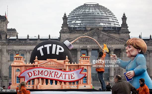 Activists of the organisation 'Foodwatch' work on a float featuring the Reichstag building housing the Bundestag and German Chancellor Angela Merkel...