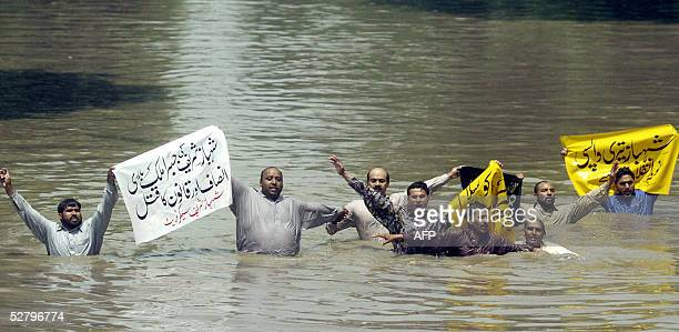 Activists of the Pakistan Muslim League shout slogans from the city canal to avoid arrest during a protest in Lahore 11 May 2005 The PMLN activists...
