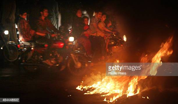 Activists of the political party Pakistan TehreekeInsaf chant anti government slogans and burn tires during a protest strike called by Imran Khan...