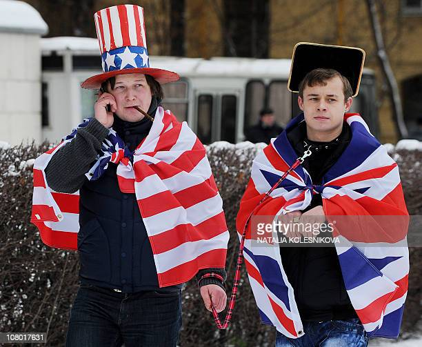 Activists of the proKremlin youth group Mestnye wearing a US flag and holding another one with a British flag on a leash rally outside the British...