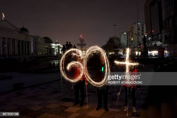 TOPSHOT Activists of the Red Cross NGO light up sparkling sticks forming the number '60' during the 'Earth Hour' event at Skopje main square on March...