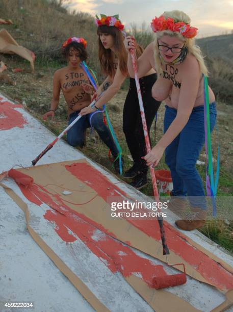 Activists of the Spanish feminist movement Femen paint in red a slogan reading 'Stop 20N' on a giant cross lying on the hill above the cementery of...