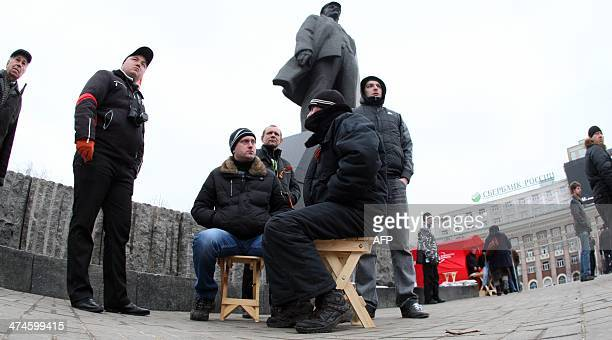 Activists of the Ukrainian Communist party sit at the Lenin monument in the center of the industrial city of Donetsk on February 24 reportedly to...