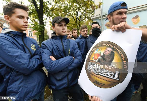 Activists of the Ukrainian farright National Corpus Ukrainian party hold a poster with an image of the logo of a popular Czech beer brand 'Kozel' and...