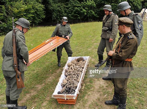 Activists of the Ukrainian Pamiat Searching Organization for victims of World War II load on July 21 2013 the remains of soldiers into a coffin...