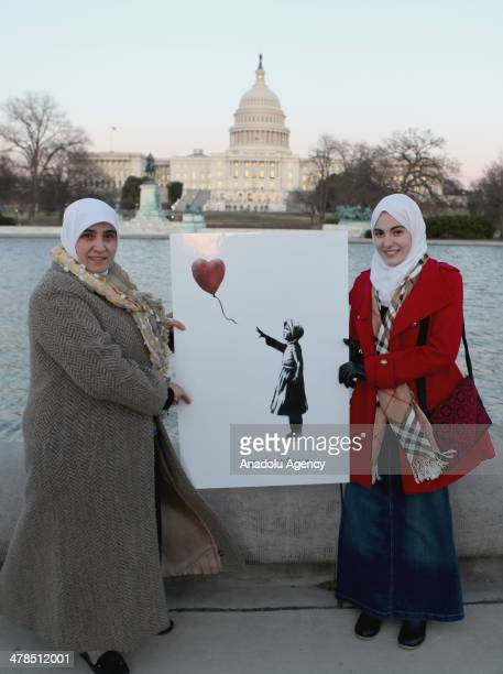 Activists of the 'With Syria' campaign hold an image of a girl holding a red heartshaped balloon by British street artist Bansky during a 'vigil of...