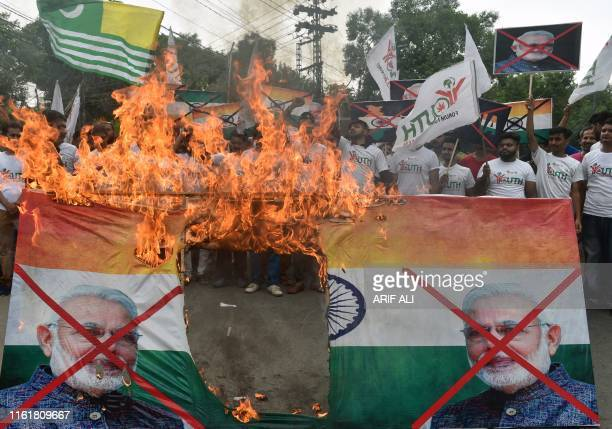 Activists of the 'Youth Forum for Kashmir' group shout slogans as they burn a picture of Indian Prime Minister Narendra Modi and the Indian flag...