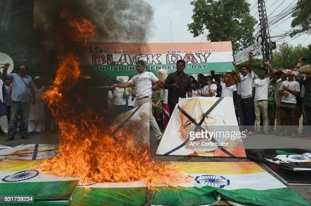 Activists of the Youth Forum of Kashmir burn images of the Indian Prime Minister Narendra Modi and Indian flags during a protest in Lahore on August...