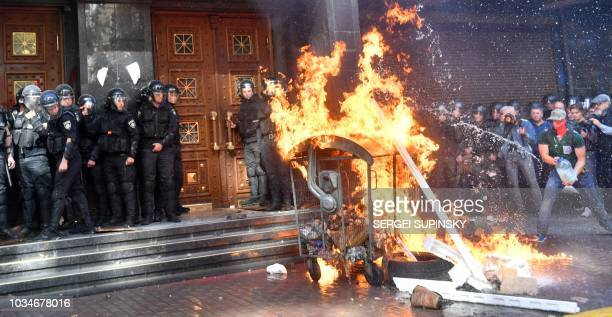 Activists of Ukrainian far-right groups burn a fire during their clashing with riot police in front of the Prosecutor General's Office in Kiev on...