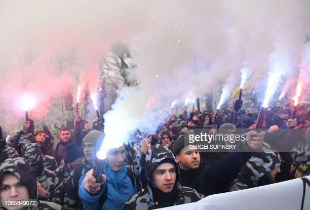 TOPSHOT Activists of Ukrainian farright groups hold flares during their rally in front of the Ukrainian parliament in Kiev on November 26 as they...