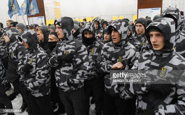 Activists of Ukrainian farright groups shout slogans during their rally at Independence Square in Kiev on November 26 as they demand to set martial...