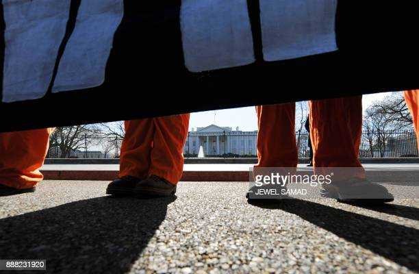 Activists of Witness Against Torture dressed as Guantanamo Bay detainees display a banner during a demonstration in front of the White House in...