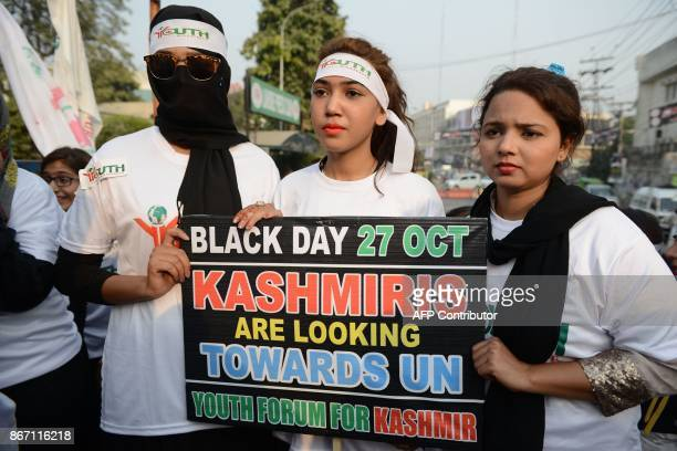 Activists of Youth Forum for Kashmir hold placard during a protest in Lahore on October 27 2017 Kashmiris protesters are observing 'Black Day' to...