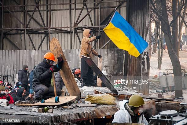 Activists on the front line on Grushevskogo st. In Kiev, Ukraine at Jan 25. 2014 where the activist with orange hard hat is defending himself against...