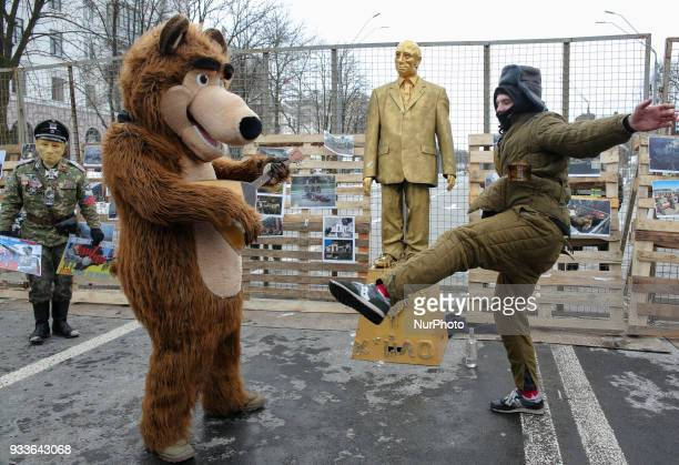 Activists one dressed in a bear with balalaika costume and another in a soviet army winter cottonpadded jacket dance around a monument of 'A Golden...