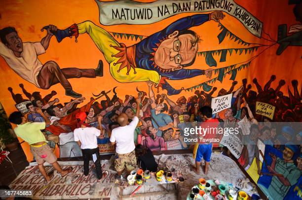 Activists paint a mural of Philippine president Benigno Aquino dressed as a clown being hounded by workers and peasants in preparation for the coming...