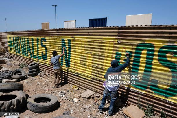 TOPSHOT Activists paint the USMexico border wall as part of the Picnic prototype Security through Friendship activity at the border near US President...