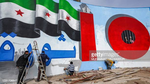 Activists paint the wall of a landmark erected in a roundabout in Syria's rebel-held northwestern city of Idlib on March 14 the wall showing a...