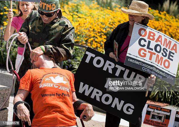 Activists participate in a mock force feeding while protesting outside the Hart Senate Office Building in Washington DC July 30 2013 Activists...