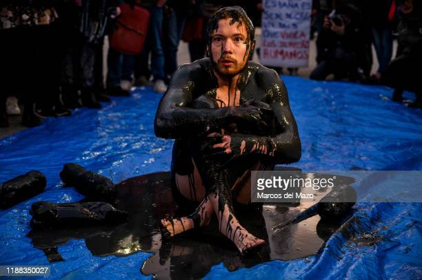 Activists performing with oil during a protest outside IFEMA where UN Climate Change Conference COP25 is being held Fridays for Future and Extinction...