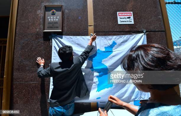 Activists place an unofficial unified Korea flag on a wall in front of the Consulate General of the Republic of Korea building in Los Angeles...