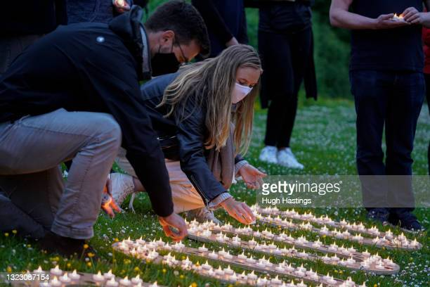 Activists place candles as they stage a pandemic vigil at sunset on Pendennis headland to remember the 3.7 million people worldwide who have died...